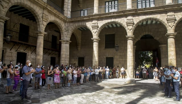 Office of the City Historian workers, wearing protective face masks as a precaution against the spread of Covid-19, gather at the Plaza de Armas to sing the National Anthem in a tribute to Eusebio Leal (Ismael Francisco/AP)