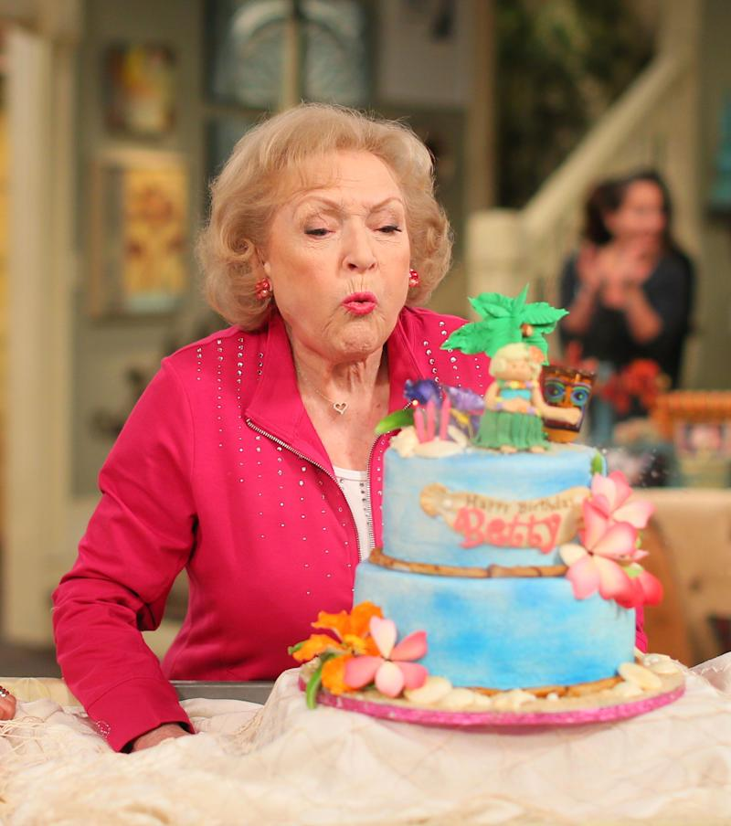 """Betty White blows out a Hawaiian themed cake that says """"Happy Birthday Betty"""""""