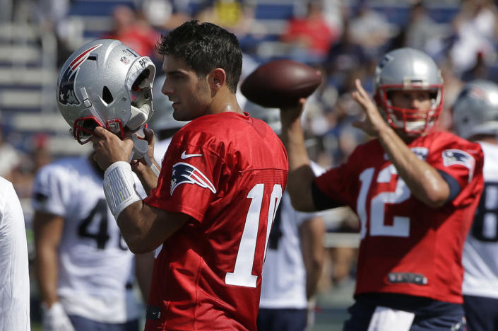 <p>New England Patriots quarterback Jimmy Garoppolo, left, removes his helmet as quarterback Tom Brady, right, winds up for a pass during an NFL football training camp practice, July 28, 2016, in Foxborough, Mass. (Photo: Steven Senne/AP)</p>
