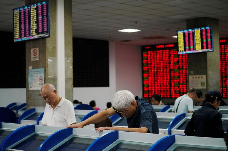 Investors look at computer screens showing stock information at a brokerage house in Shanghai, China September 7, 2018. REUTERS/Aly Song/Files