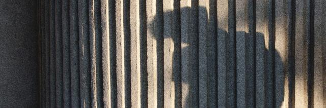 shadow of a boy with backpack against a ribbed concrete wall