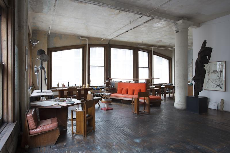 """When Italian artist Francesco Clemente moved to New York in 1981 with his wife Alba and their two children, they chose to live on one of the city's most dangerous streets. After buying a large loft there, they bought a number of essential furnishings including a couch, a shelf, and a small table and chairs, designed by Frank Lloyd Wright, """"for a few hundred dollars apiece."""" This view of the studio shows some of those original pieces alongside designs by Ettore Sottsass and Jean Prouvé. A large Fernwood Spirit Statue from Vanuatu frames a portrait of Rene Richard by Clemente on the right. In the distance the Julian Schnabel–designed dining table can be seen in the kitchen area, which became the setting for many of Alba's legendary meals. Some of the details of their dinner parties are recorded in Andy Warhol's diaries."""