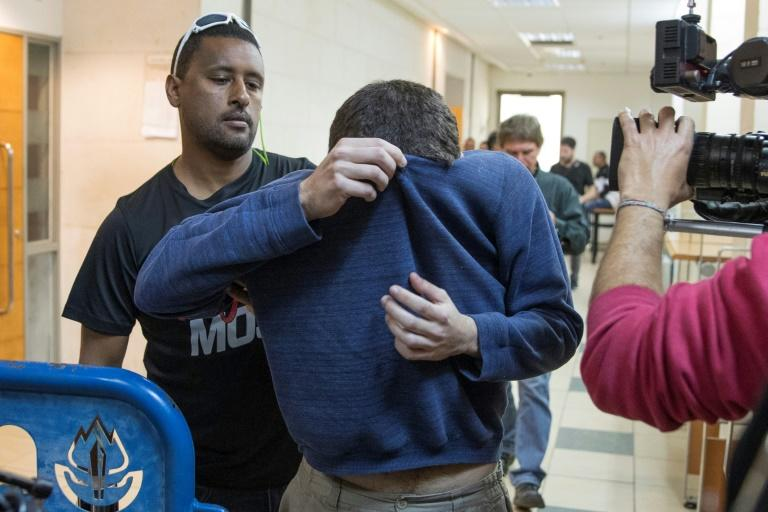 A US-Israeli Jewish teenager accused of making dozens of anti-Semitic bomb threats in the United States and elsewhere is escorted by guards as he leaves an Israeli court after his arrest