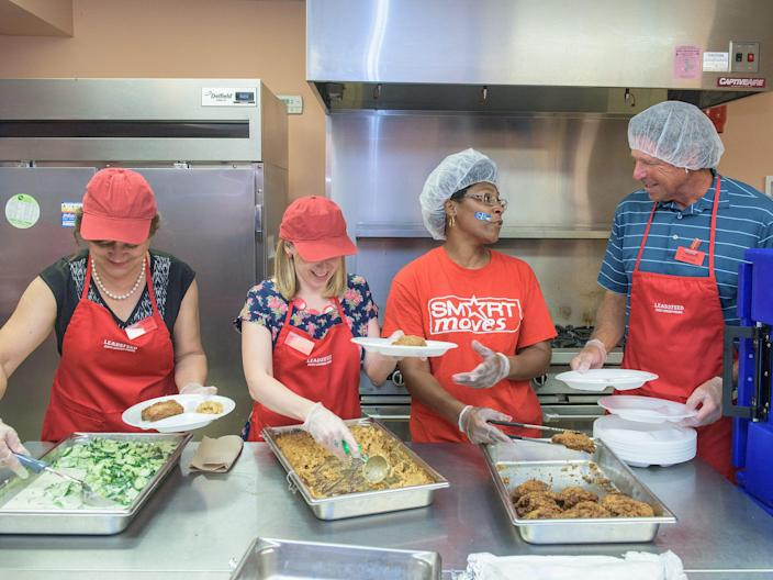 David Novak, then Yum! Brands executive chairman (right), in a kitchen with educators Inez Estrada Lovio and Coco Wolf (left) and a volunteer on July 21, 2015 in Louisville, Kentucky.
