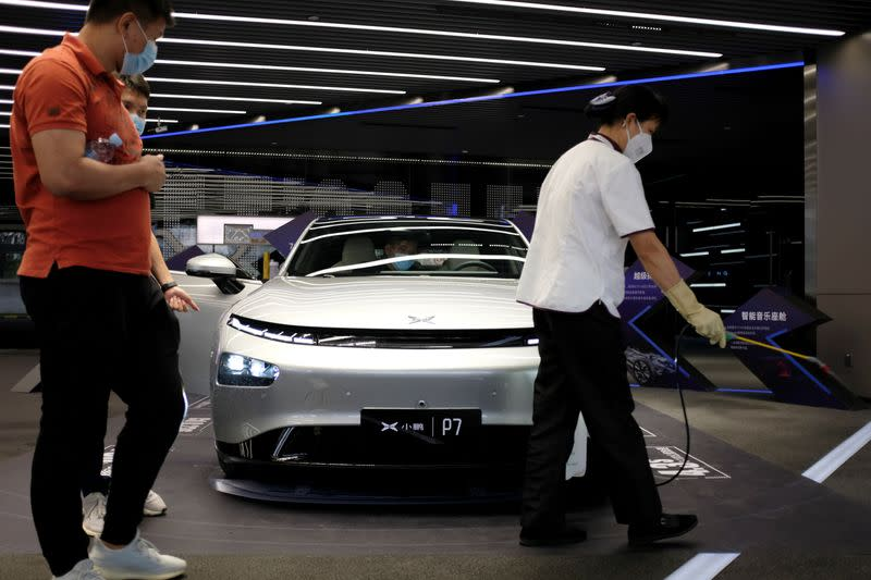 Staff sprays disinfectant near Xpeng P7 sedan displayed at XPeng Motors headquarters in Guangzhou