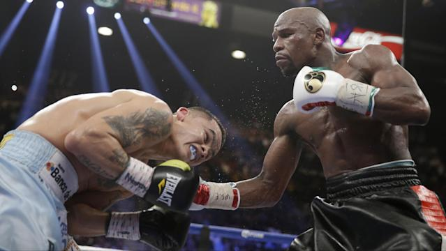 Floyd Mayweather Jr., right, connects with a right to the head of Marcos Maidana, from Argentina, in their WBC-WBA welterweight title boxing fight Saturday, May 3, 2014, in Las Vegas. (AP Photo/Isaac Brekken)