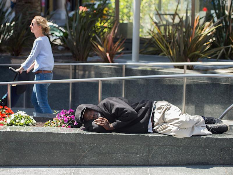 A homeless man sleeps in San Francisco, where more than 7,000 people have nowhere to live: AFP/Getty