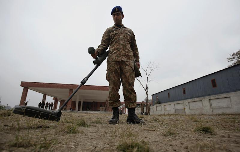 In this Wednesday, Jan. 8, 2014, photo, a Pakistani soldier scans an area with a metal detector during a training session at the Counter IED Explosives and Munitions School, in Risalpur, Pakistan. Militants in Pakistan have become devilishly ingenious about where they plant improvised explosive devices, a type of bomb responsible for thousands of wounds and deaths in Pakistan. They've been found strapped to children's bicycles, hidden inside water jugs and even hung in tree branches. (AP Photo/Anjum Naveed)