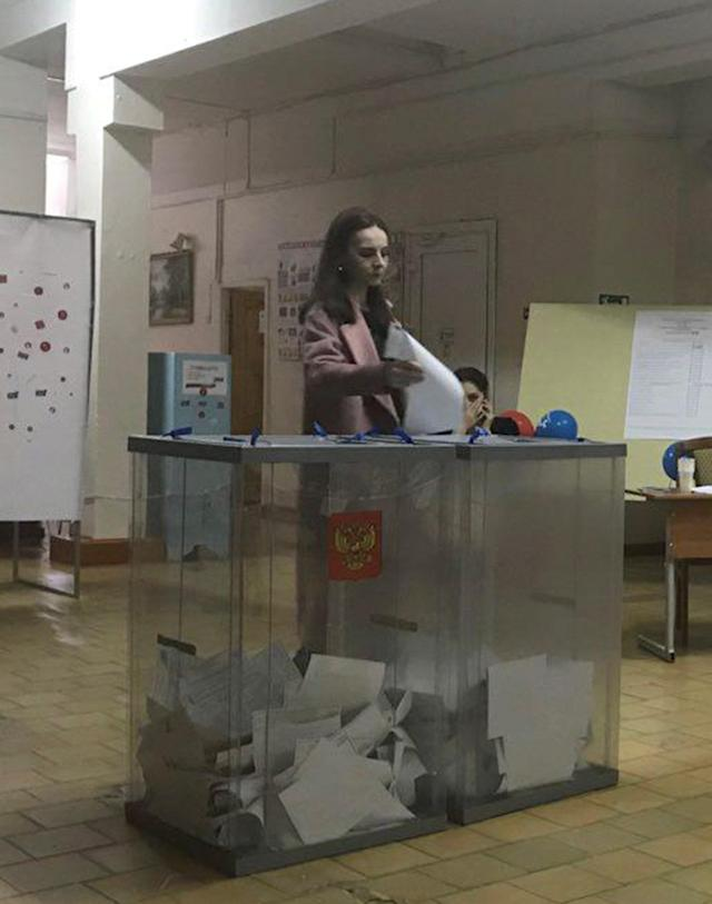 A voter casts a ballot at a polling station number 216 during the presidential election in Ust-Djeguta, Russia March 18, 2018. The voter, asked by a Reuters reporter to explain why she was voting multiple times, ignored the question and walked away. Picture taken March 18, 2018. REUTERS/Maria Tsvetkova
