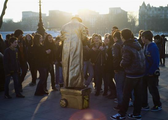 A performance artist performs to tourists along the south bank on the River Thames in London March 13, 2012.