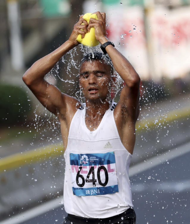 Nepal's Gopi Chandra Park sponges himself down with water during the men's marathon at the 18th Asian Games in Jakarta, Indonesia, Saturday, Aug. 25, 2018. (AP Photo/Dita Alangkara)