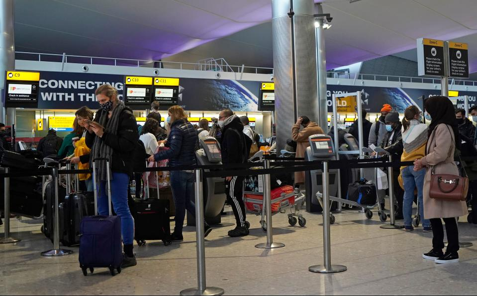 "Customers wearing face covers queue at a TAP Air Portugal check-in desk in the departures hall at Terminal 2 of Heathrow Airport in west London on December 21, 2020, as a string of countries around the world banned travellers arriving from the UK, due to the rapid spread of a new, more-infectious coronavirus strain. - Prime Minister Boris Johnson was to chair a crisis meeting Monday as a growing number of countries blocked flights from Britain over a new highly infectious coronavirus strain the UK said was ""out of control"". (Photo by Niklas HALLE'N / AFP) (Photo by NIKLAS HALLE'N/AFP via Getty Images)"