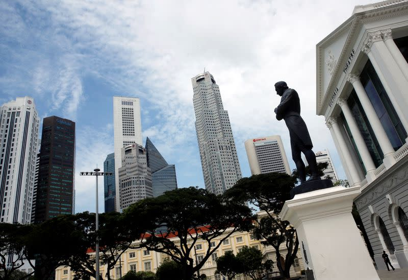 A man passes a statue of Sir Stamford Raffles next to the skyline of Singapore