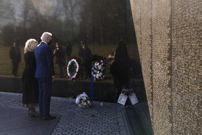 President Joe Biden and first lady Jill Biden pause after laying flowers as they visit the Vietnam Veterans Memorial to commemorate Vietnam War Veterans Day, Monday, March 29, 2021, in Washington. (AP Photo/Evan Vucci)