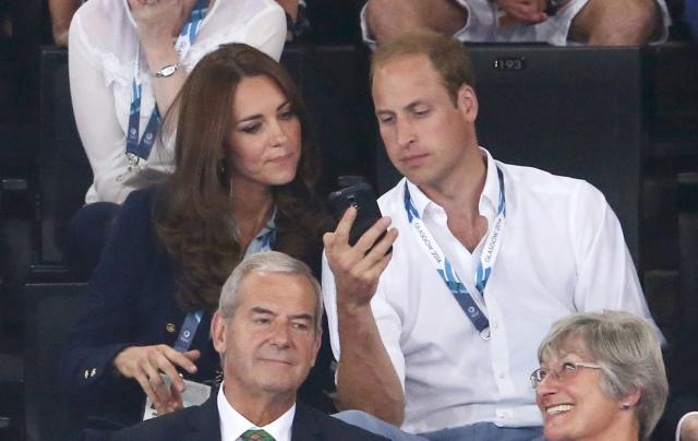 Catherine, Duchess of Cambridge looks at a smartphone with with her husband Prince William as they watch artistic gymnastics at the 2014 Commonwealth Games in Glasgow, Scotland, July 28, 2014. REUTERS/Phil Noble (BRITAIN - Tags: SPORT GYMNASTICS ROYALS)