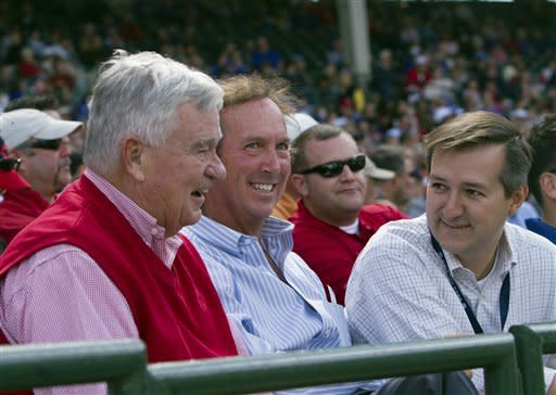 Chicago Cubs chairman Tom Ricketts, right, chats with Cincinnati Reds owner Bob Castellini, left, and Vice Chairman Tom Williams, during the baseball game between the teams in Chicago on Thursday, Sept. 20, 2012. (AP Photo/Charles Cherney)