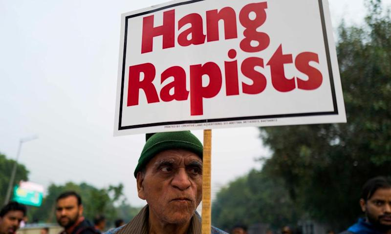 A protester holds a placard calling for rapists to be hanged