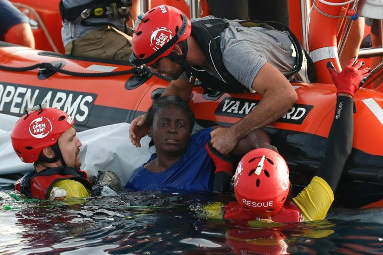 Members of the Spanish NGO Proactiva Open Arms rescue a woman in the Mediterranean sea in July 2018