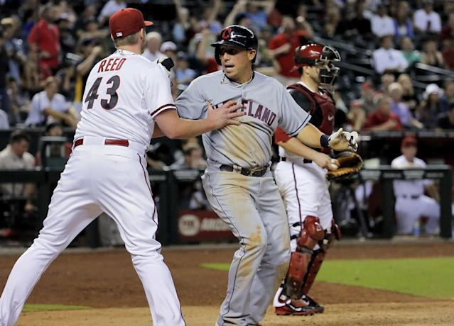 Cleveland Indians' Asdrubal Cabrera, center, collides with Arizona Diamondbacks pitcher Addison Reed (43) as Miguel Montero looks away after Cabrera scored during the ninth inning of a baseball game, Tuesday, June 24, 2014, in Phoenix. (AP Photo/Matt York)