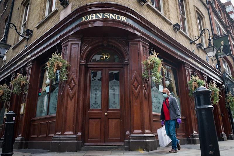 LONDON, ENGLAND - JUNE 19: A person wearing a protective face mask walks past a temporarily closed pub named after the founding father of epidemiology John Snow, on June 19, 2020 in London, England. Despite no guidelines coming from the government on how pubs, restaurants, hotels, and cafes should re-open, many are still pushing ahead to welcome customers back on July 4th 2020. The UK service industry went in to lockdown during the coronavirus pandemic on March 23rd 2020. (Photo by Leon Neal/Getty Images)
