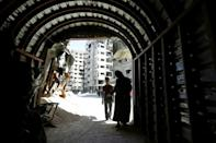 Syrians enter a tunnel leading to an underground hospital in Douma, in eartern Ghouta, a subterranean network of tunnels and makeshift wards and operating rooms beneath the former rebel enclave