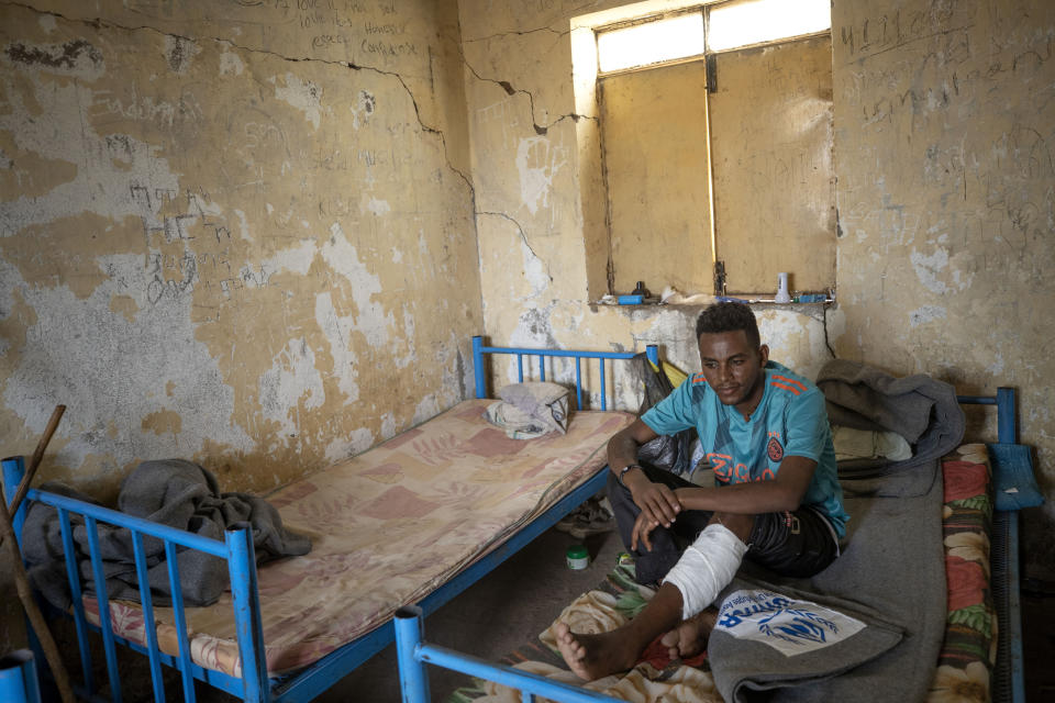 Hiwet Aregawi, 24, a Tigrayan who was allegedly attacked by the 'Fano' militia, young Amhara militias, rests his wounded leg in a shelter at the Hamdeyat Transition Center near the Sudan-Ethiopia border, eastern Sudan, Tuesday, Dec. 15, 2020. No one knows how many thousands of people have been killed in Tigray since the fighting began on Nov. 4, but the United Nations has noted reports of artillery strikes on populated areas, civilians targeted and widespread looting. (AP Photo/Nariman El-Mofty)
