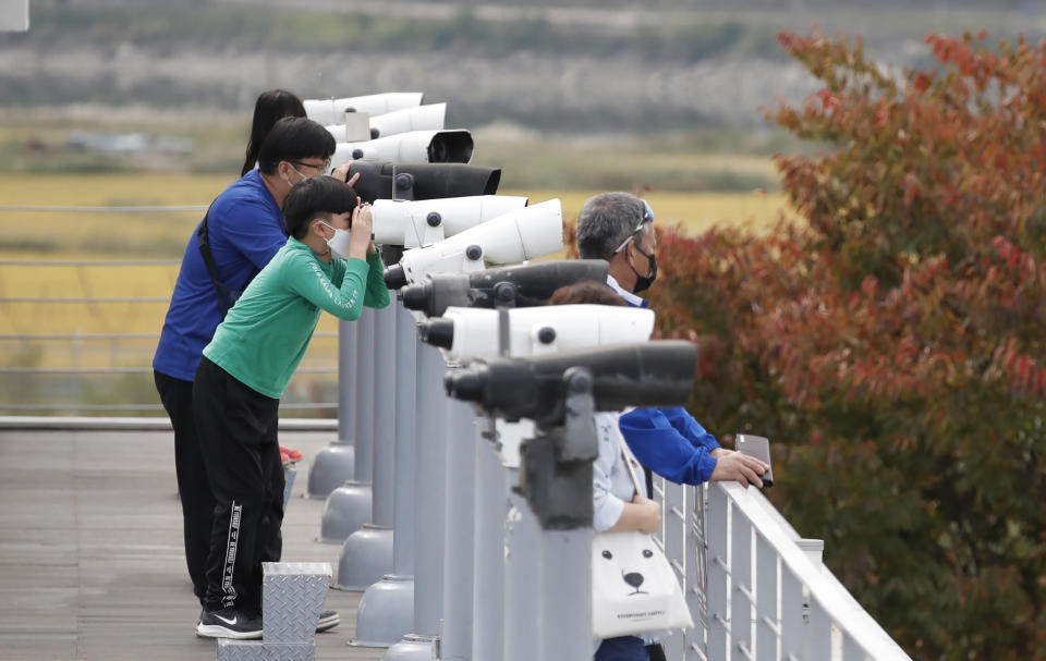 "Visitors wearing face masks use binoculars to view from the Imjingak Pavilion in Paju, South Korea, Sunday, Oct. 11, 2020. North Korean leader Kim Jong Un warned that his country would ""fully mobilize"" its nuclear force if threatened as he took center stage at a military parade that unveiled what appeared to be a new intercontinental ballistic missile and other weapons Saturday. (AP Photo/Lee Jin-man)"