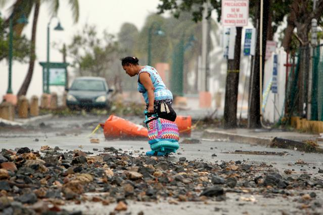 <p>A woman pulls a travel case on a rock scattered road in the aftermath of Hurricane Irma in Fajardo, Puerto Rico, on Sept. 7, 2017. (Photo: Ricardo Arduengo/AFP/Getty Images) </p>