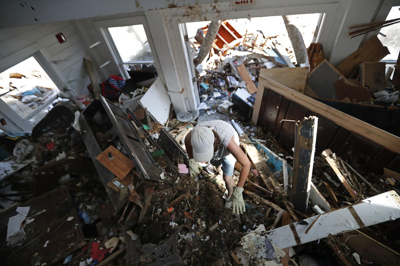 <p>Amy Hay, an employee of the the Driftwood Inn for 18 years, sifts through debris for valuables in the aftermath of Hurricane Michael in Mexico Beach, Fla., Wednesday, Oct. 17, 2018. (Photo: Gerald Herbert/AP) </p>