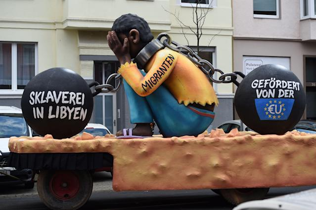 "<p>A carnival float, depicting a migrant with chains with the writings ""Slavery in Libya"" and ""supported by the EU"", is pictured during a carnival parade on Rose Monday on Feb. 12, 2018 in Duesseldorf, western Germany. (Photo: Patrik Stollarz/Getty Images) </p>"