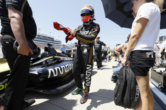 FILE - In this July 19, 2019, file photo, James Hinchcliffe stands next to his car during qualifying for the IndyCar Series auto race at Iowa Speedway in Newton, Iowa. McLaren will return to full-time IndyCar competition next season for the first time since 1979 in a partnership with existing team Arrow Schmidt Peterson Motorsports. The new venture will be renamed Arrow McLaren Racing SP and rely on Arrow SPM's current infrastructure.(AP Photo/Charlie Neibergall, File)