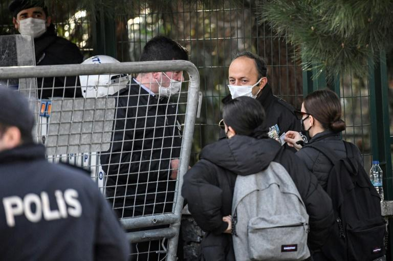 Students show their IDs to enter the campus as Turkish anti-riot police officers guard the main gate of the Bogazici university on January in Istanbul during a protest against the appointment of the new rector by the Turkish president.