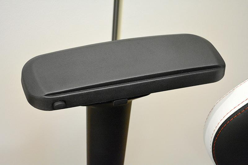 Pushing the button toward the front allows the armrest to move either forward or backward. The middle button activates the side adjustment mechanism.