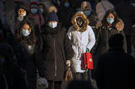 People wearing face masks to protect against the spread of the coronavirus walk along a street during the morning rush hour in Beijing, Wednesday, Dec. 30, 2020. Beijing has urged residents not to leave the city during the Lunar New Year holiday in February, implementing new restrictions and mass testings after several coronavirus infections last week. (AP Photo/Mark Schiefelbein)