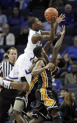Memphis guard Antonio Barton (2) goes to the basket over Southern Mississippi guards Angelo Johnson, bottom, and Rashard McGill in the first half of an NCAA college basketball game on Wednesday, Jan. 11, 2012, in Memphis, Tenn. (AP Photo/Lance Murphey)