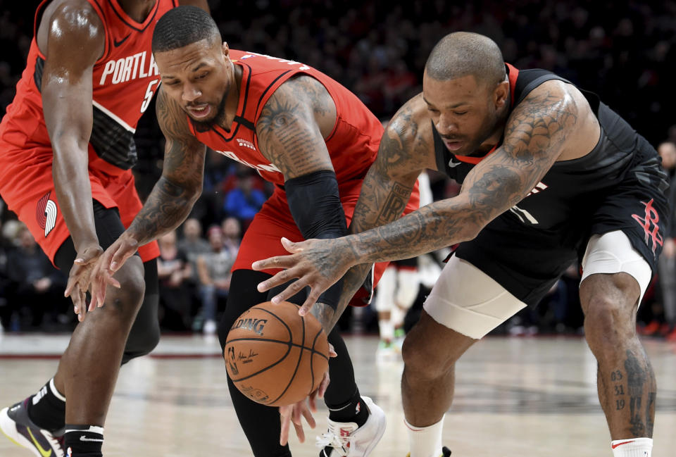 Portland Trail Blazers guard Damian Lillard, left, and Houston Rockets forward P.J. Tucker, right, go after a loose ball during the first half of an NBA basketball game in Portland, Ore., Wednesday, Jan. 29, 2020. (AP Photo/Steve Dykes)