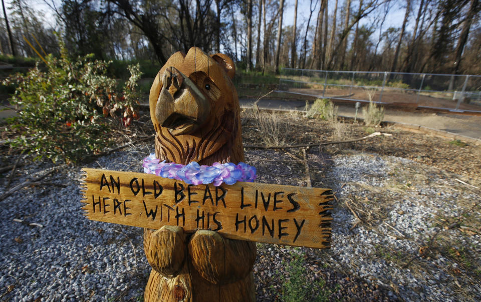 FILE - In this Thursday, Oct. 24, 2019, photo, a wooden bear still stands at a home that was lost in last year's Camp Fire in Paradise, Calif. Only a handful of homes have been rebuilt in the community that lost nearly 9,000 residences in last year's Camp Fire. (AP Photo/Rich Pedroncelli)