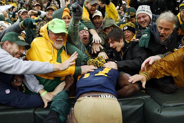 Fans celebrate with Green Bay Packers' Eddie Lacy after his touchdown run during the first half of an NFL football game against the Cleveland Browns Sunday, Oct. 20, 2013, in Green Bay, Wis. (AP Photo/Tom Lynn)