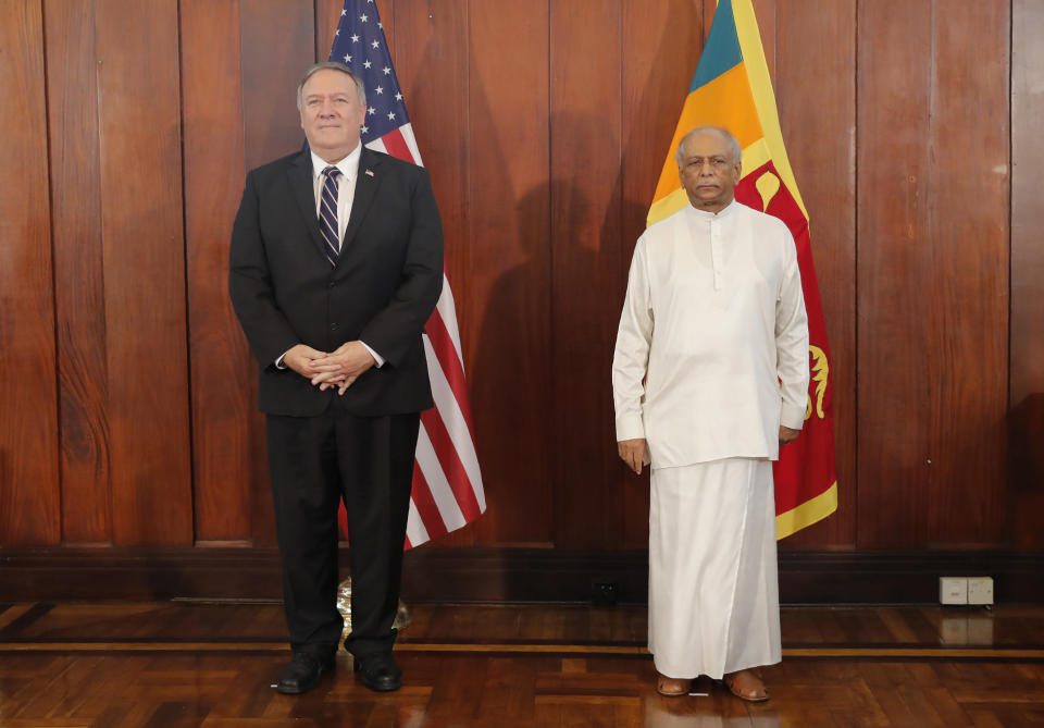 U.S. Secretary of State Mike Pompeo and Sri Lankan Foreign Minister Dinesh Gunawardena stand for photographs before their meeting in Colombo, Sri Lanka, Wednesday, Oct. 28, 2020. Pompeo plans to press Sri Lanka to push back against Chinese assertiveness, which U.S. officials complain is highlighted by predatory lending and development projects that benefit China more than the presumed recipients. The Chinese Embassy in Sri Lanka denounced Pompeo's visit to the island even before he arrived there, denouncing a senior U.S. official's warning that the country should be wary of Chinese investment. (AP Photo/Eranga Jayawardena, Pool)