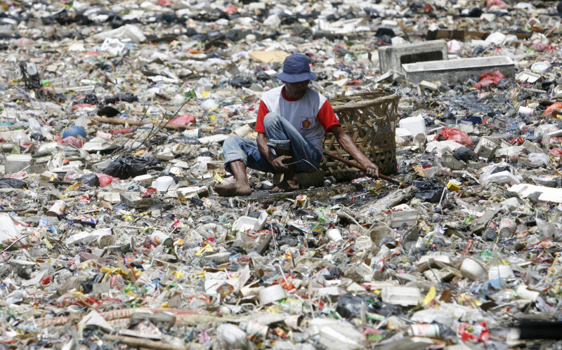 A man collects plastic goods in a river littered with garbage in Jakarta. (Photo: Supri Supri/Reuters)