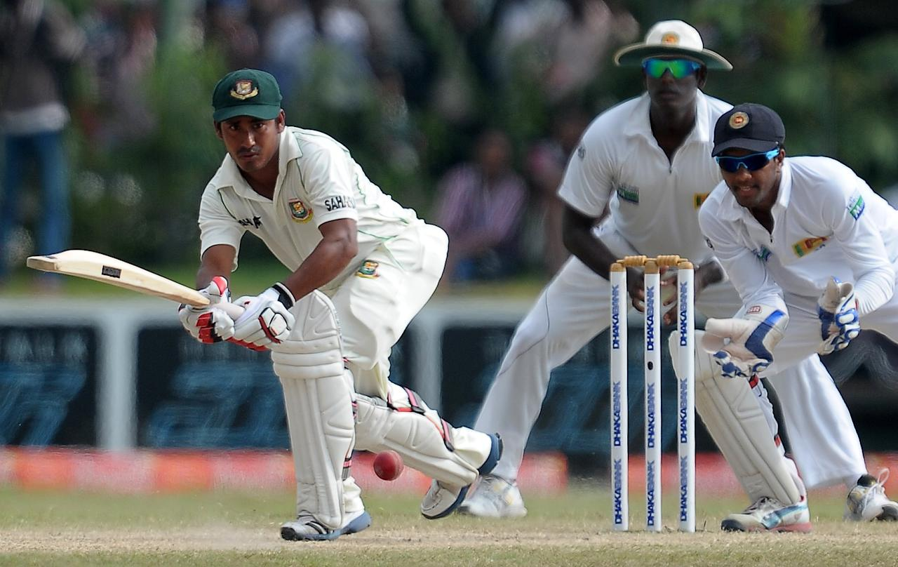 Bangladeshi cricketer Mohammad Ashraful (L) is watched by Sri Lankan wicketkeeper Dinesh Chandimal as he plays a shot during the final day of the opening Test match between Sri Lanka and Bangladesh at the Galle International Cricket Stadium in Galle on March 12, 2013.  The opening Test between Sri Lanka and Bangladesh ended in a tame draw on the fifth and final day at the Galle International Stadium on Tuesday. AFP PHOTO/ LAKRUWAN WANNIARACHCHI        (Photo credit should read LAKRUWAN WANNIARACHCHI/AFP/Getty Images)