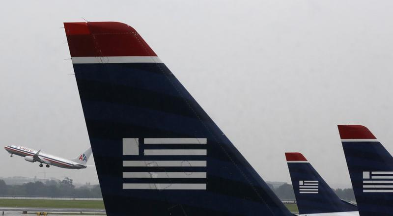 U.S. Airways jets are lined up at Reagan National Airport as an American Airlines jet takes off in Washington