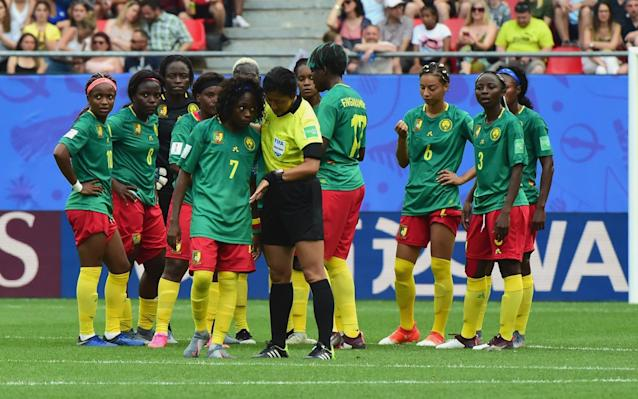 Referee Qin Liang tries to calm the Cameroon players - Getty Images Europe