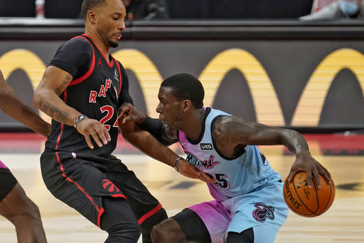 Miami Heat guard Kendrick Nunn (25) pushes off Toronto Raptors guard Norman Powell (24) as he drives up the court during the second half of an NBA basketball game Wednesday, Jan. 20, 2021, in Tampa, Fla. (AP Photo/Chris O'Meara)