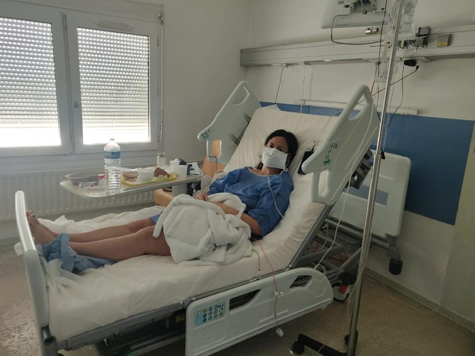 Pictured is Intan Clement lying in her hospital bed wearing a surgical mask after contracting coronavirus.