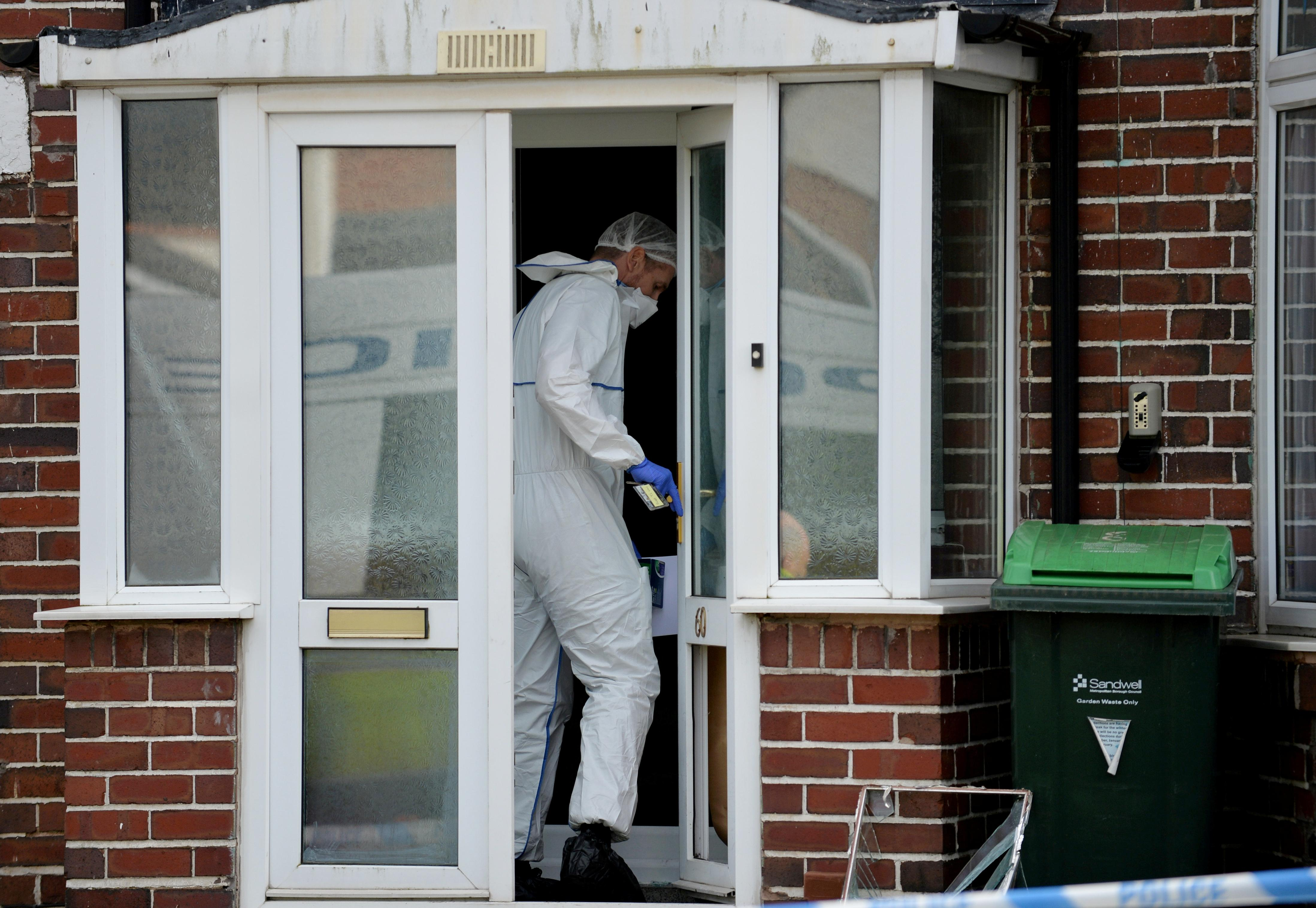 "Police forensics at the scene in Moat Road in Oldbury, West Mids, where the bodies of a middle-aged couple were found in their home this morning. February 25, 2020. See SWNS story SWMDmurders. A 25-year-old man was arrested on suspicion of double murder today (Tues) after the bodies of a middle-aged couple were found in their home. Police officers forced their way into a house in Moat Road in Oldbury, West Mids., at 4am after receiving calls regarding the welfare of the couple. Inside the property officers found the bodies of a woman, 54, and a 52-year-old man who were pronounced dead at the scene. At 5.30am detectives arrested a 25-year-old man at an address in nearby Smethwick. Police are not confirming if the man was the victims' parents but say they are treating the murders as a ""domestic-related incident"". A West Midlands Police spokesperson said: ""We've arrested a man on suspicion of murder after the bodies of two people were found in Oldbury today."