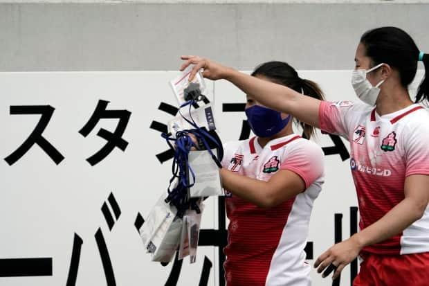 Japanese rugby players collect their protective masks and IDs after a test event in preparation for the Tokyo 2020 Olympic Games at Tokyo Stadium on Thursday.