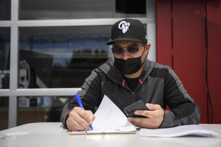 Amid a year of unemployment, one job applicant fills out paperwork for hospitality employment during a job fair on June 23, 2021 in Torrance, California. (Photo by Patrick T. FALLON/AFP)