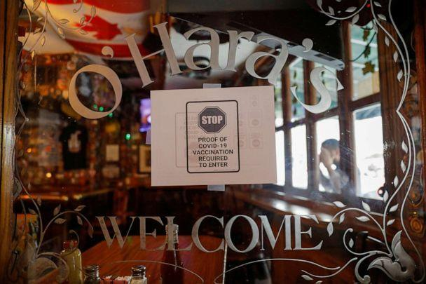 PHOTO: Signage is seen in the entrance of O'Hara's, a bar near the World Trade Center, as the vaccine mandate began in New York, Aug. 17, 2021. (Andrew Kelly/Reuters)