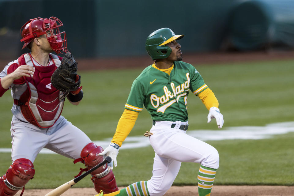 Oakland Athletics' Tony Kemp, right, hits an RBI-triple in front of Los Angeles Angels catcher Max Stassi during the third inning of a baseball game in Oakland, Calif., Monday, June 14, 2021. (AP Photo/John Hefti)
